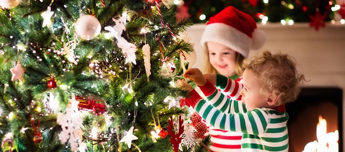 happy little kids in matching red and green striped pajamas decorate christmas tree in beautiful living - Kids Decorating For Christmas
